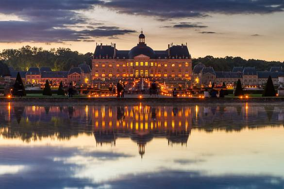 Image of a grand château by a lake in France at sunset