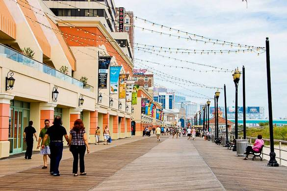 Image of people walking on the Atlantic City boardwalk lined with casinos and hotels