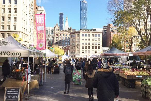 Image of people strolling through Union Square Greenmarket with stalls of farm produce