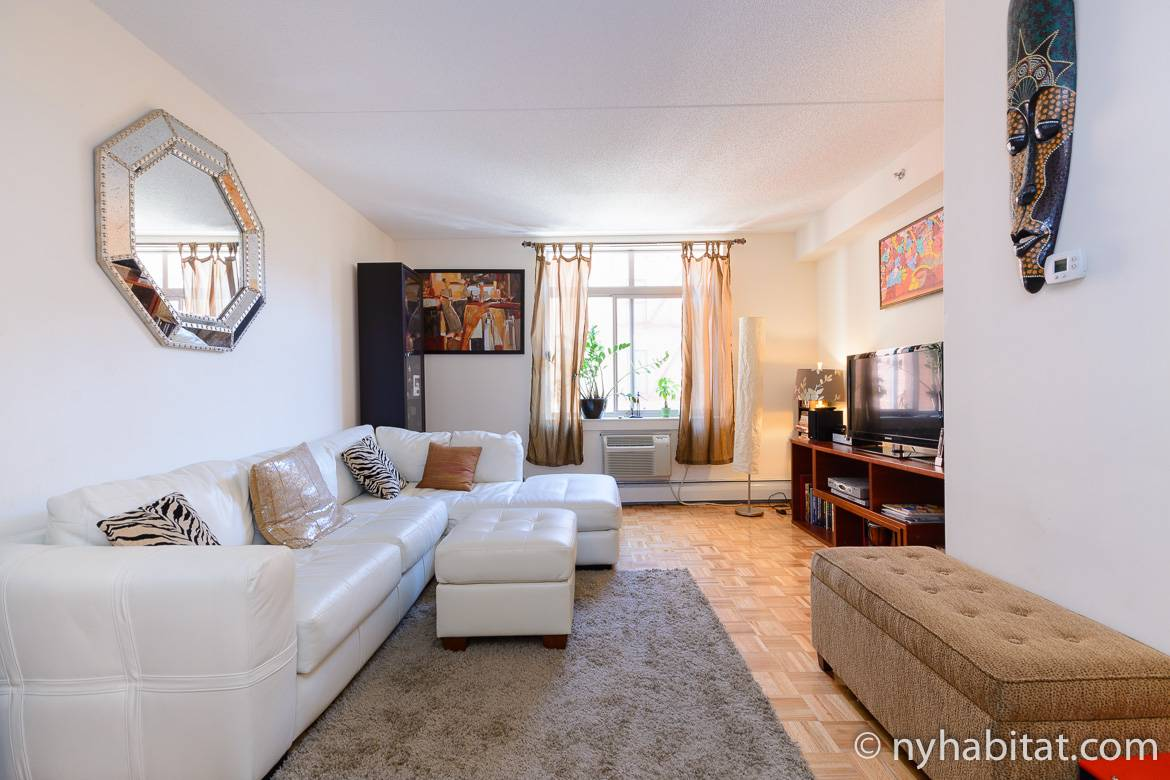 Image of living room of NY-16163 with white leather sectional sofa and African art on the walls