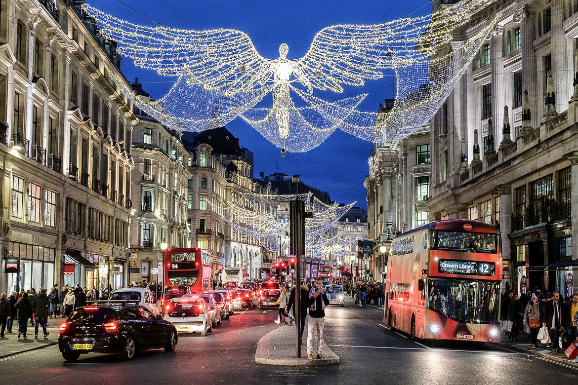 Image of angels made with lights strung above the street with double decker red buses beneath