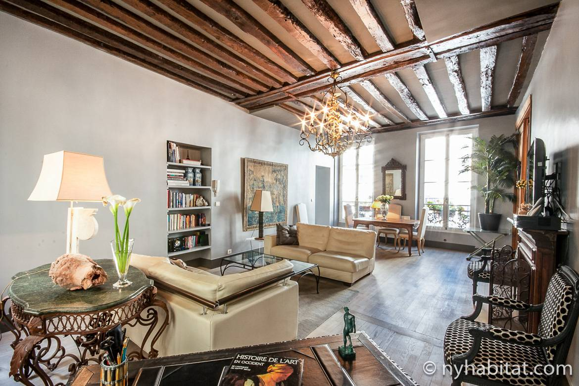 Image of living room of PA-1344 in the Marais with wood beam ceiling, chandelier, bookcases and sofas