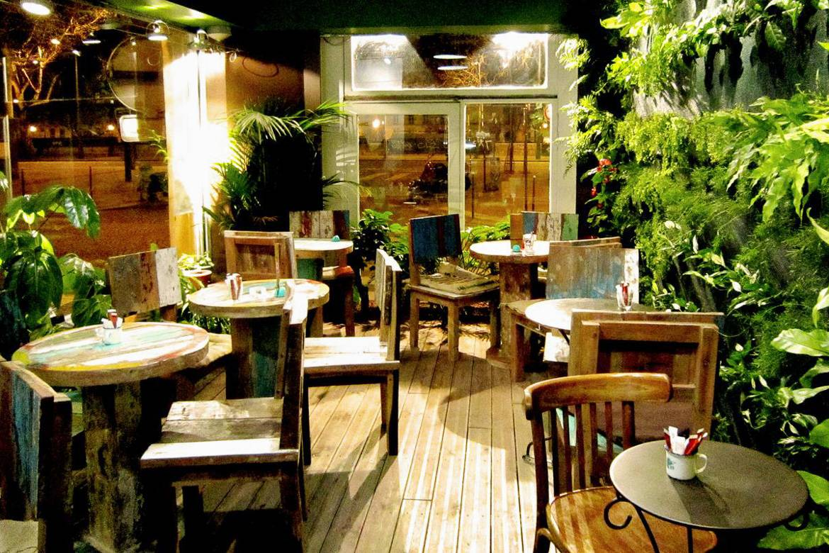 Image of La Caféothèque coffee spot with plants lining the walls