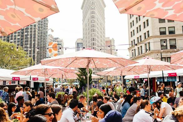 Image of people eating under sun umbrellas in the Flatiron District