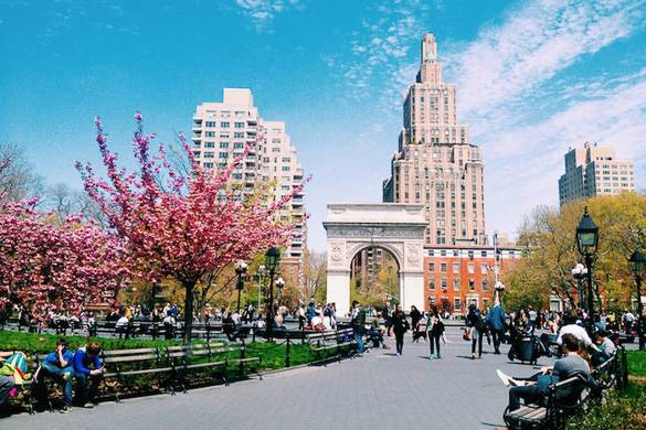 Image of arch in Washington Square Park in Greenwich Village with flowering trees and benches