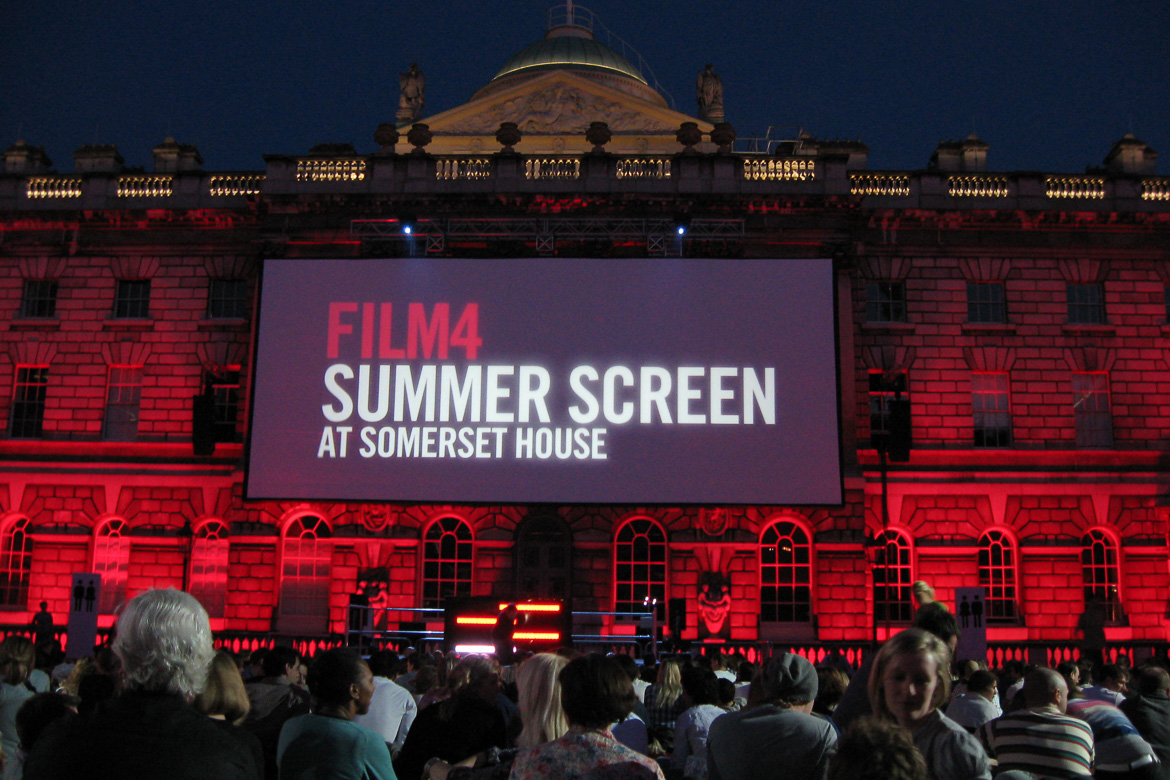 Image of Somerset House in London with movie screen on the façade and moviegoers in the foreground