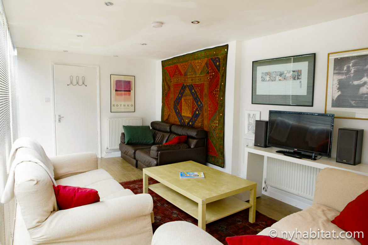 Image of living room in LN-1468 with white sofas, television and a red tapestry on the wall