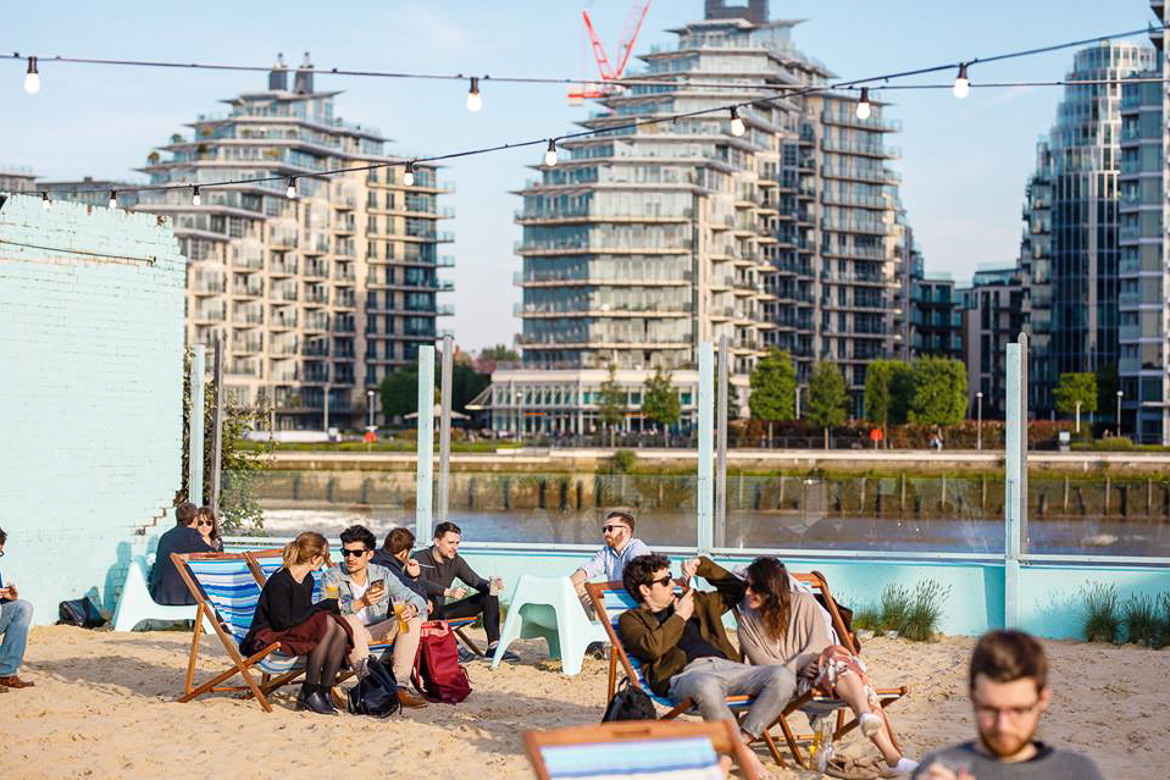 Image of people sitting in lounge chairs at Neverland London's Fulham beach club with the Thames river in the background.