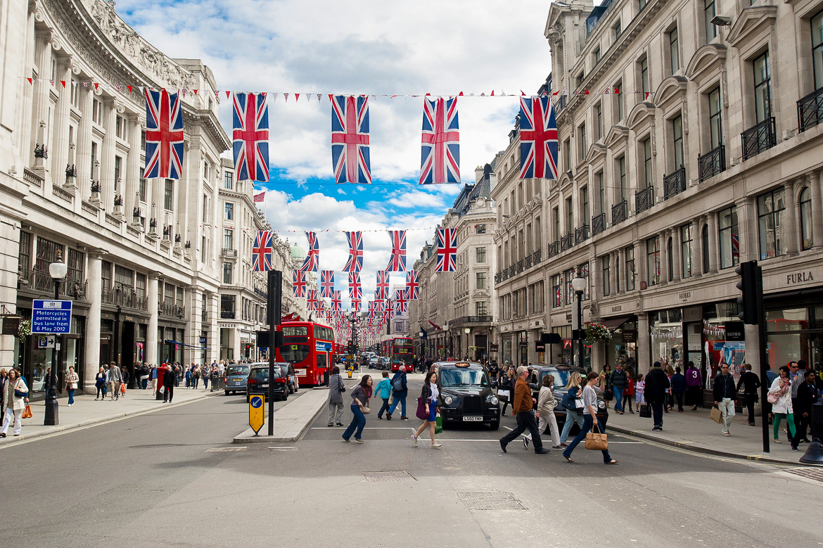 Image of people crossing a busy London street with the Union Jack flag overhead