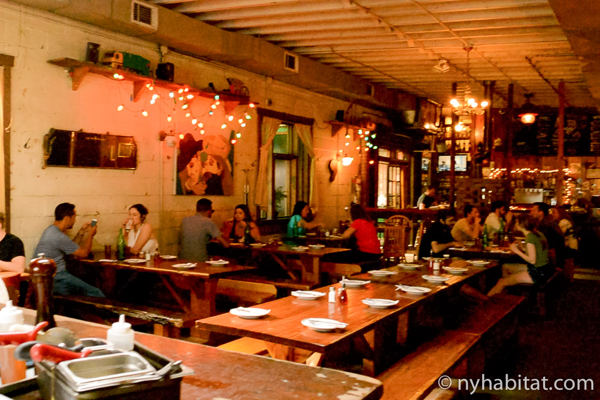 Image of young people enjoying food and drinks at a bar in Bushwick, Brooklyn.