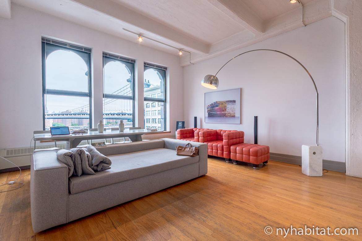 Image of living area in NY-14834 with couch, lamp, and windows opening to Manhattan Bridge view.
