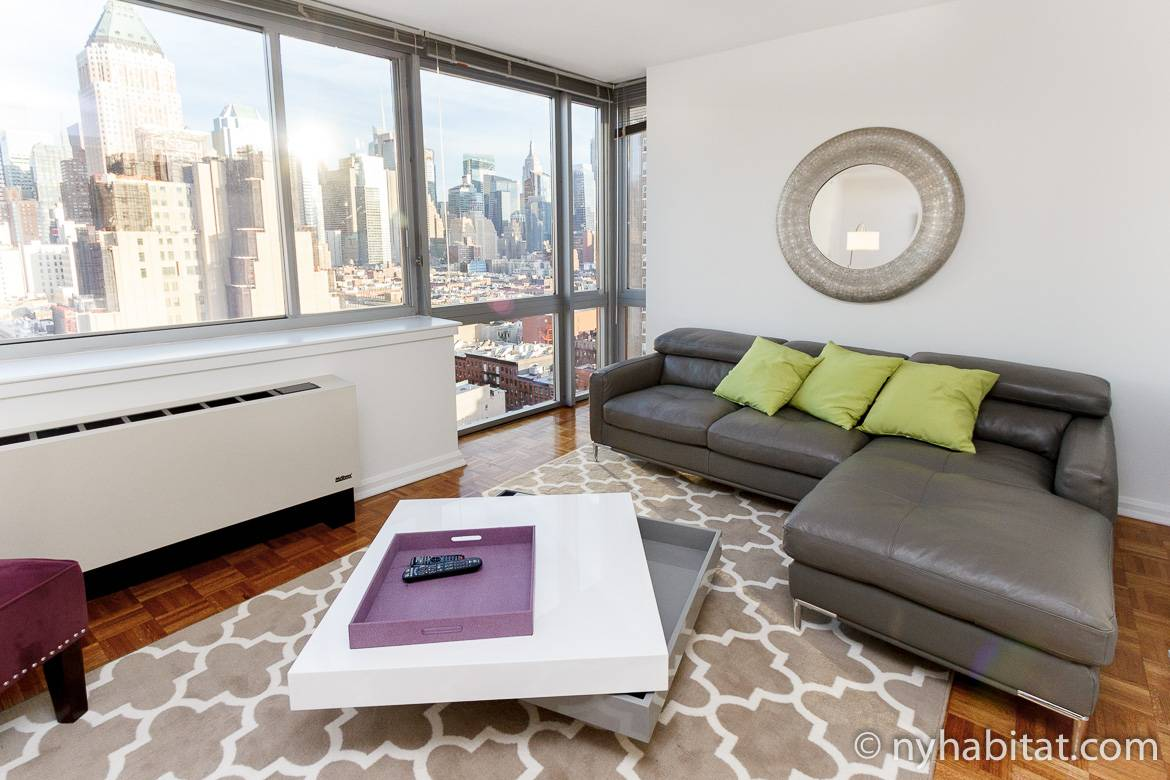 Image of living area of NY-16172 with sofa, coffee table and large windows.