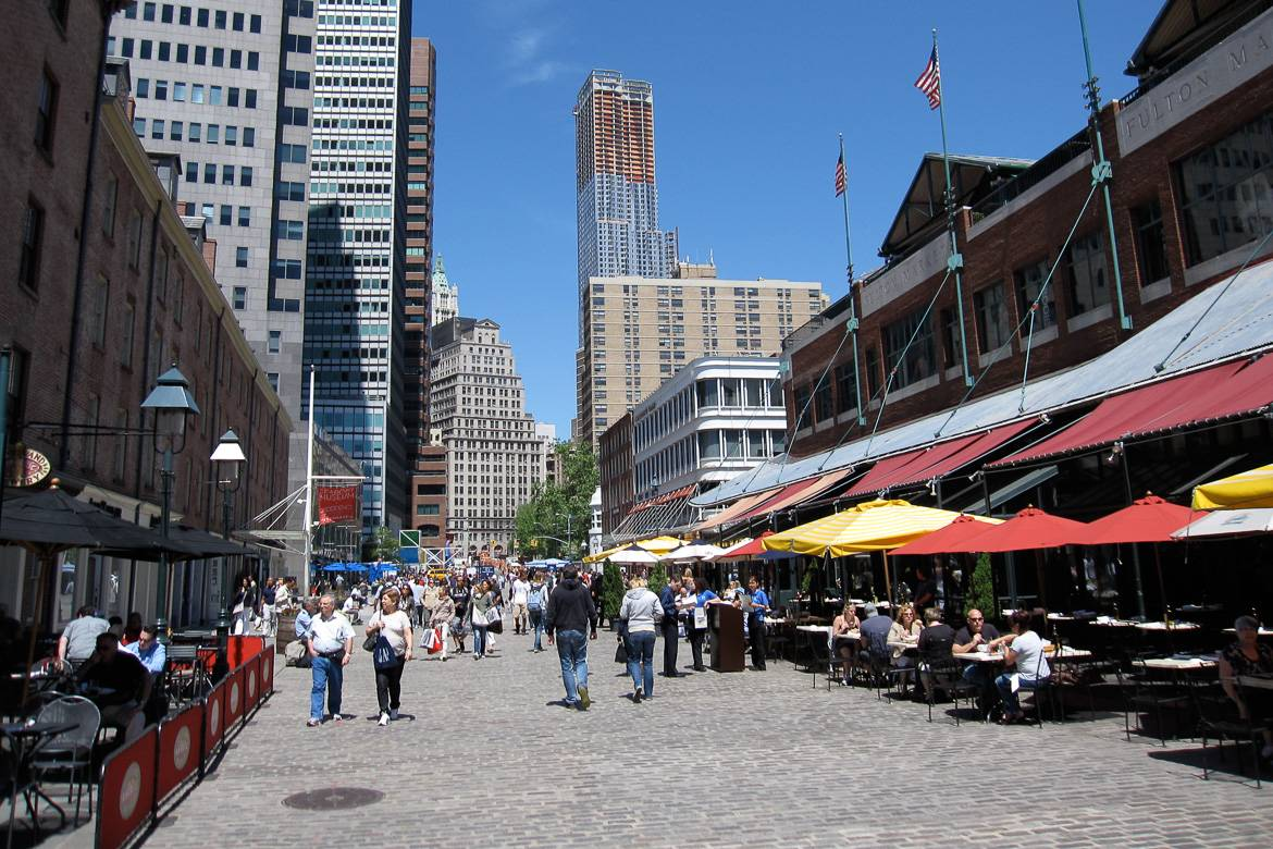 Image of South Street Seaport on a sunny day lined with tables and people dining outdoors.