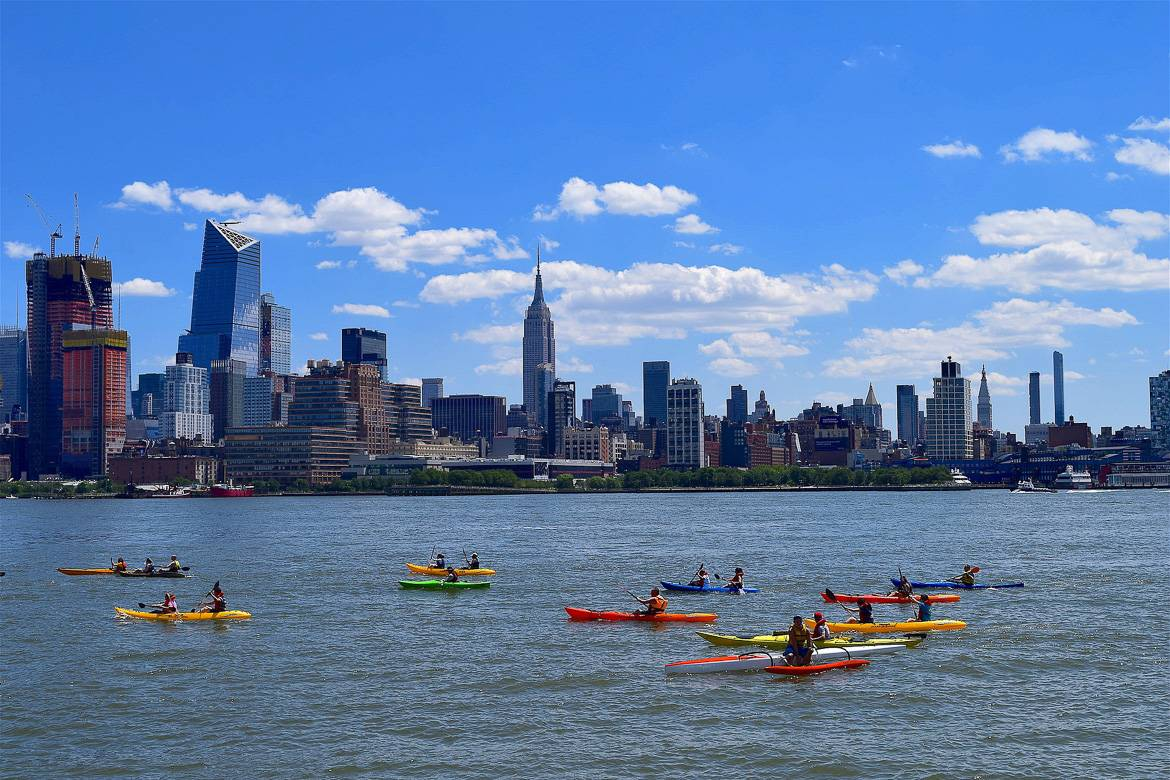Image of people kayaking on the river in New York City with the city skyline in the background.