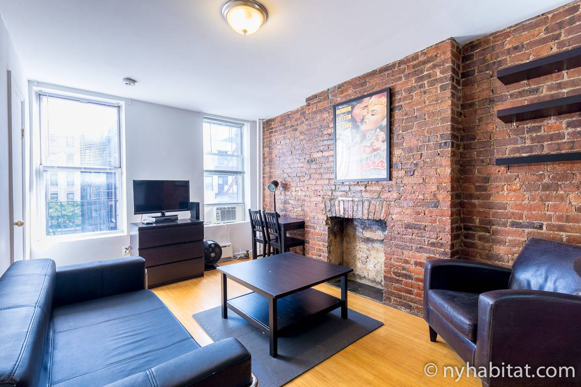 Image of living area with leather furniture and decorative fireplace in studio apartment NY-17291