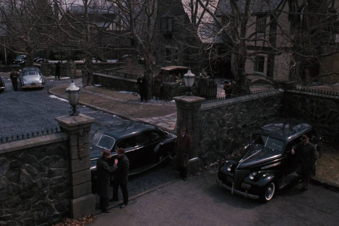 Image still of gates and cars outside the Corleone residence in the 1972 film The Godfather.