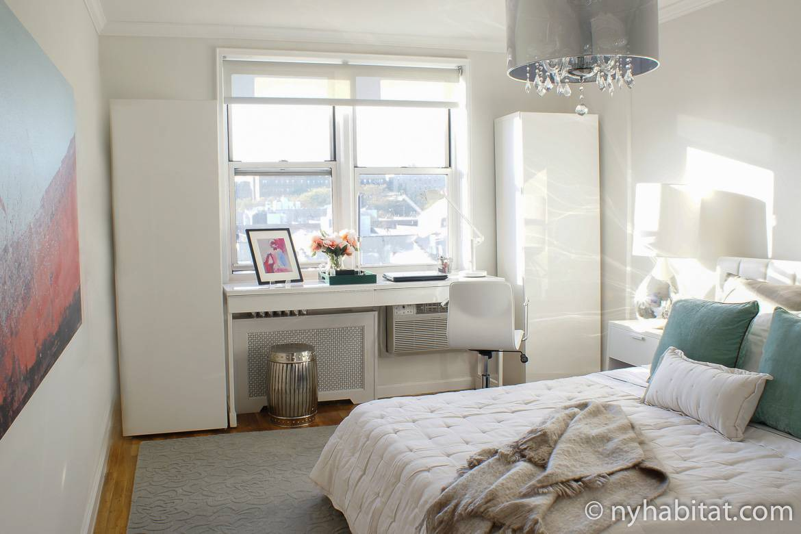Image of bedroom in NY-17527 with queen-sized bed, desk, chandelier and window.