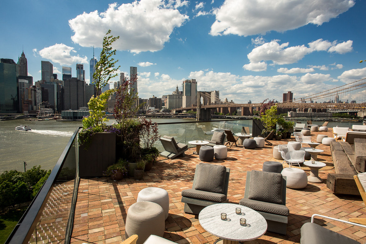 Image of the 1 Hotel Brooklyn Bridge rooftop bar with views of the East River and Manhattan skyline.