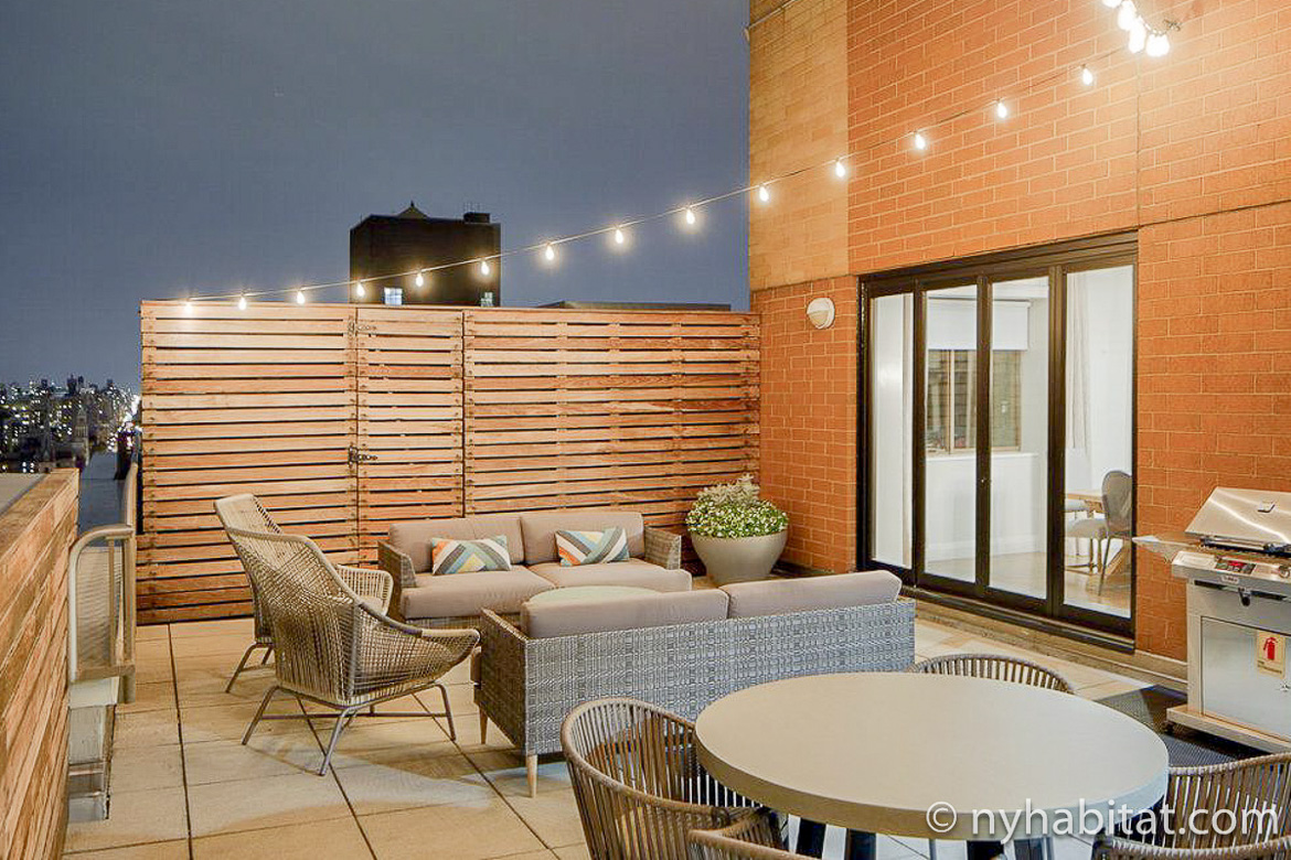 Image of rooftop lounge with patio furniture and string lights at furnished apartment NY-17339