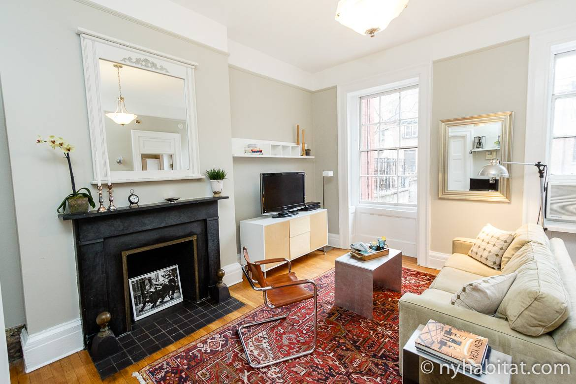 Image of living area of NY-15108 with fireplace, sofa, chair and television.