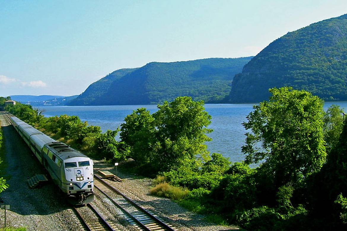 Image of MTA Metro North train traveling alongside the Hudson River and mountains.