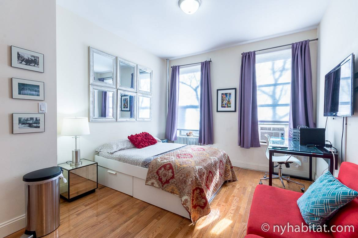 Image of living area in NY-17406 with double bed, two windows and artwork.
