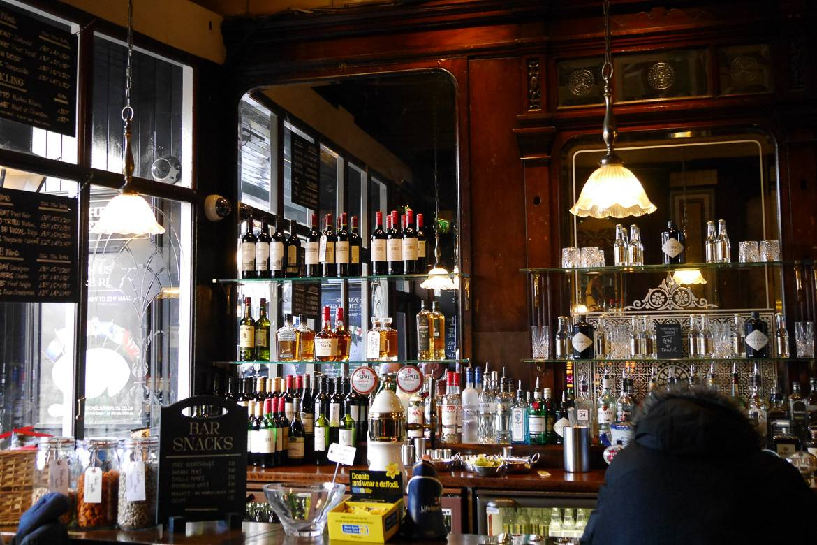 Image of wooden bar area in an English pub stocked with liquor.