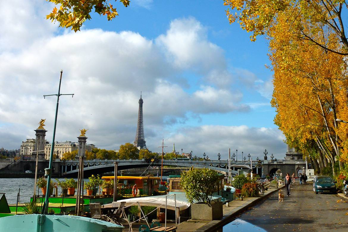 Image of the Seine River with Pont Alexandre and Eiffel Tower in the background in autumn.