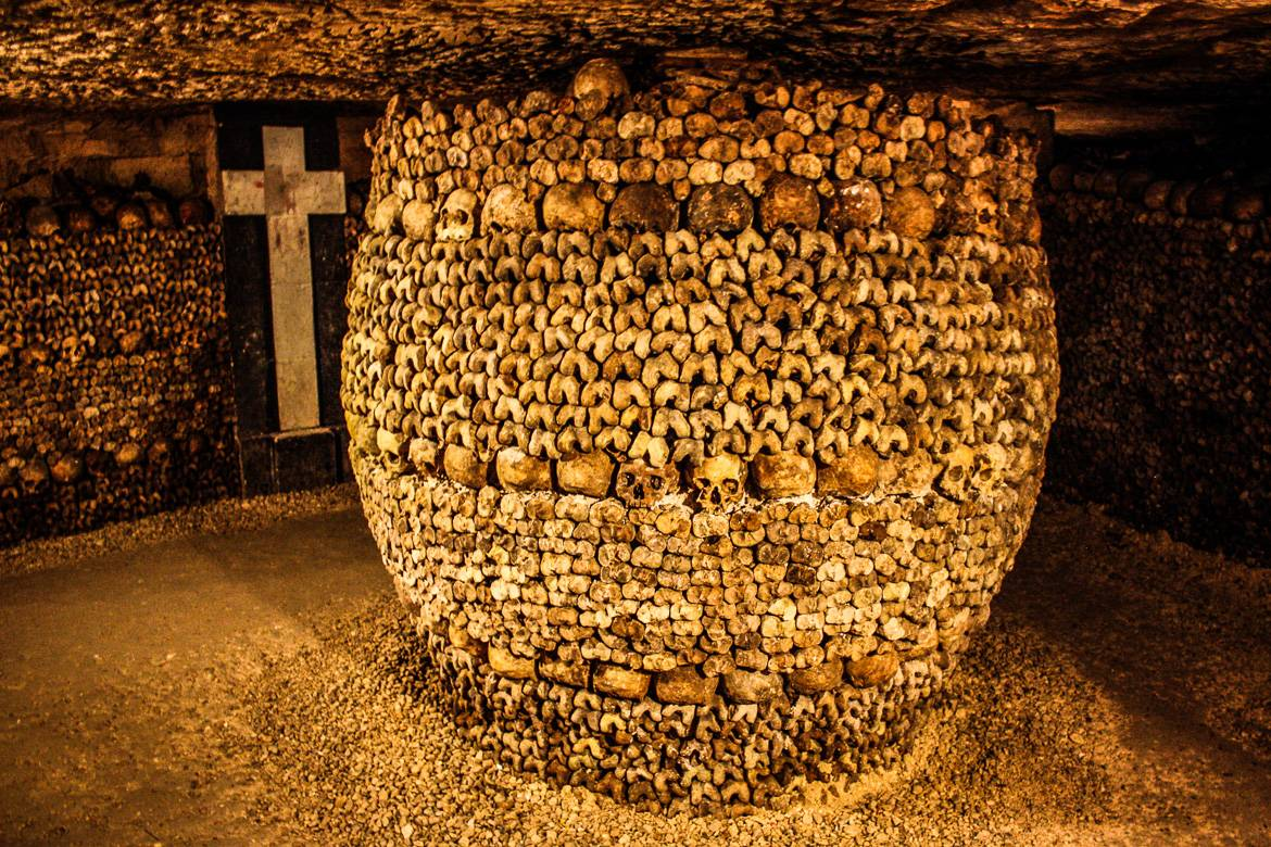 Image of column made of human skulls and bones in the Catacombs of Paris.