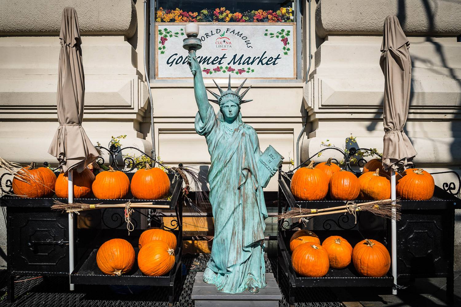 Image of a miniature Statue of Liberty surrounded by pumpkins.