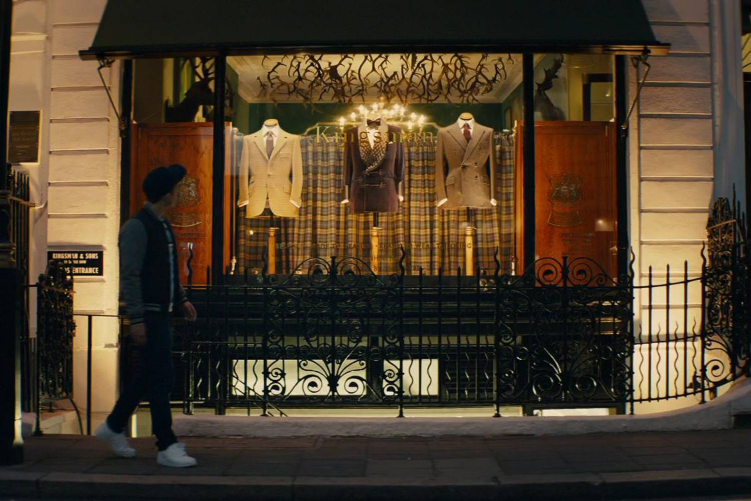 Image still of actor Taron Egerton walking on the street in front of the Kingsman headquarters in Kingsman: The Secret Service.