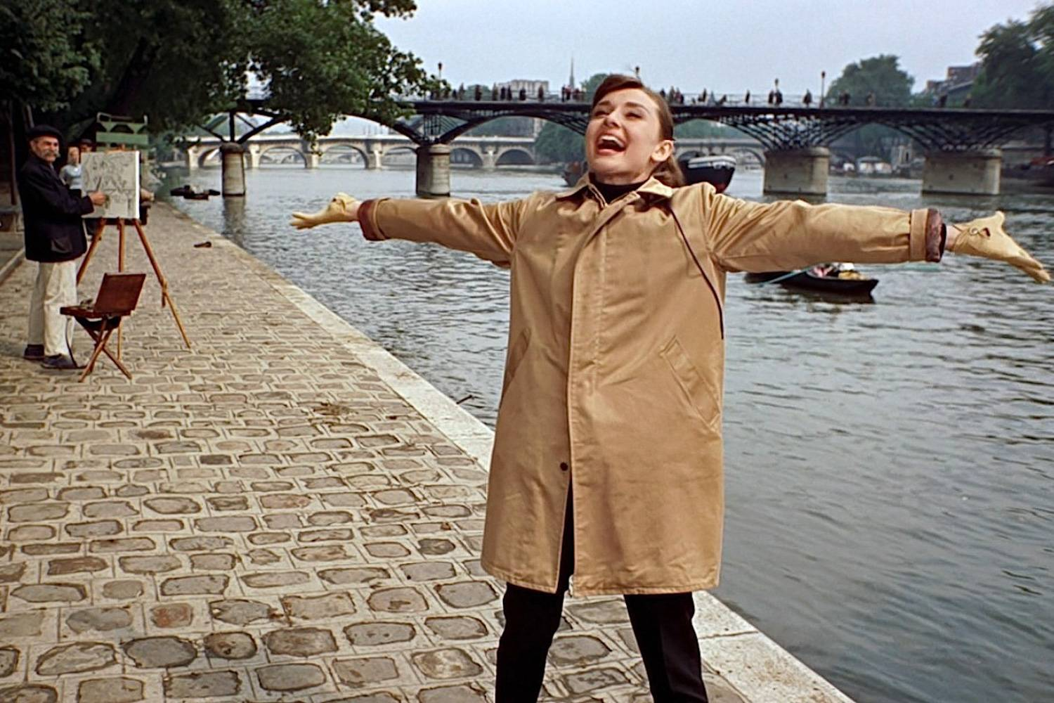 Image still of actress Audrey Hepburn singing on the banks of the Seine in the film Funny Face.
