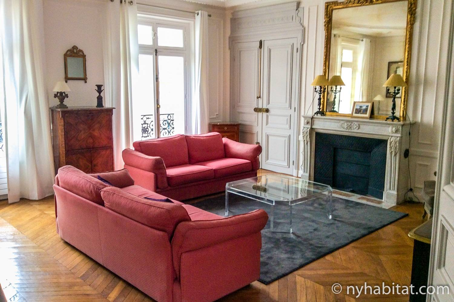 Image of living area of PA-3348 with decorative fireplace, French windows and red sofa.