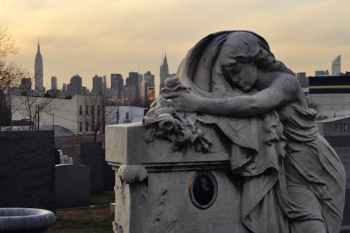 Image of grave with statue in Cavalry Cemetery in Queens, New York at sunset.