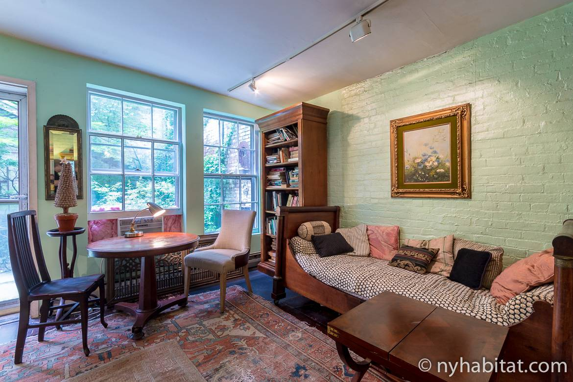 Image of living area of NY-15343 in Chelsea with antique sofa, table and chairs and wooden bookshelf.