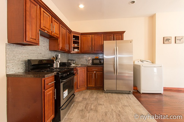 Image of kitchen with oven and stainless steel refrigerator in NY-17086