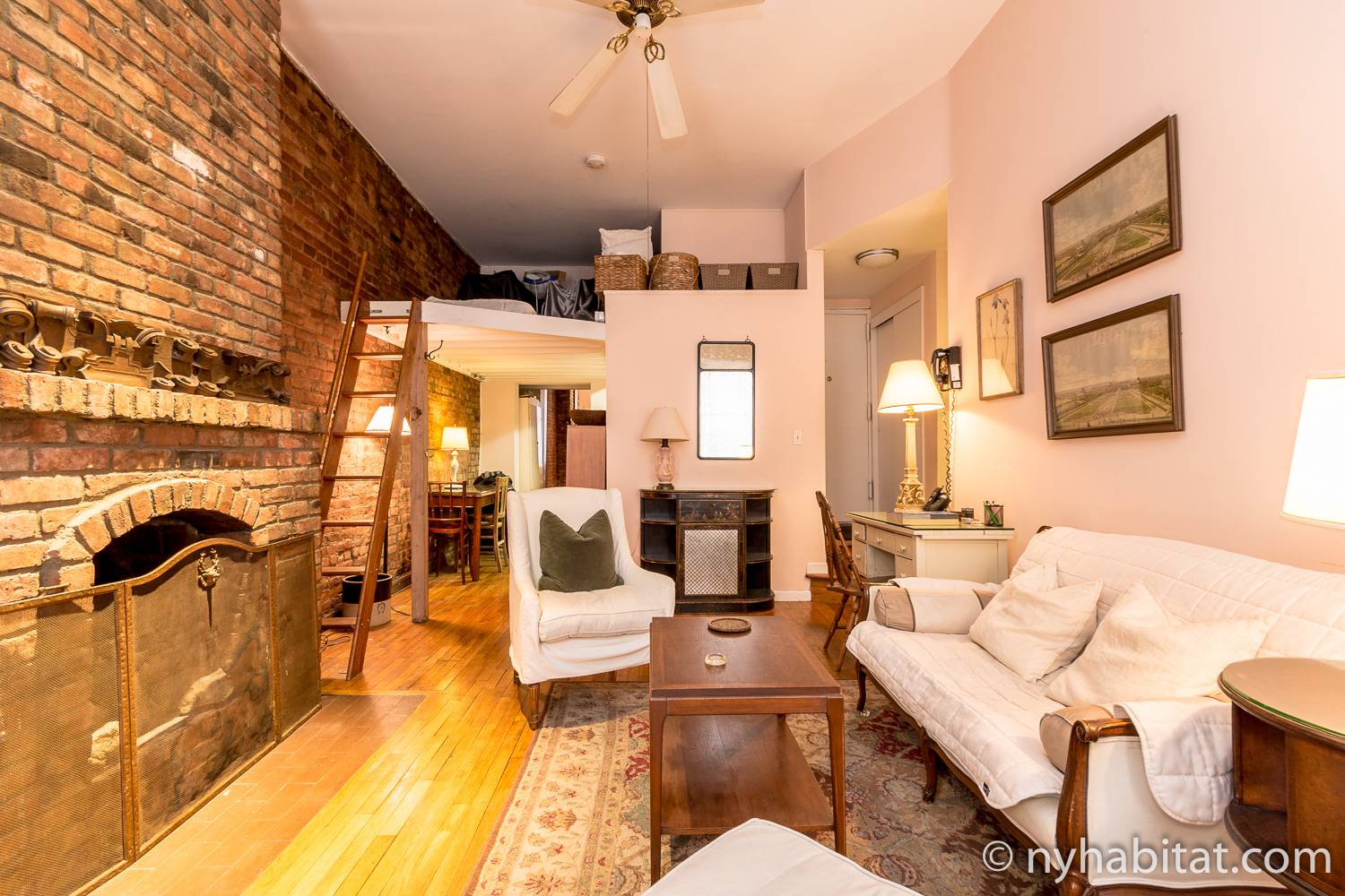 Image of living area of NY-12100 with decorative fireplace, loft storage area and sofa
