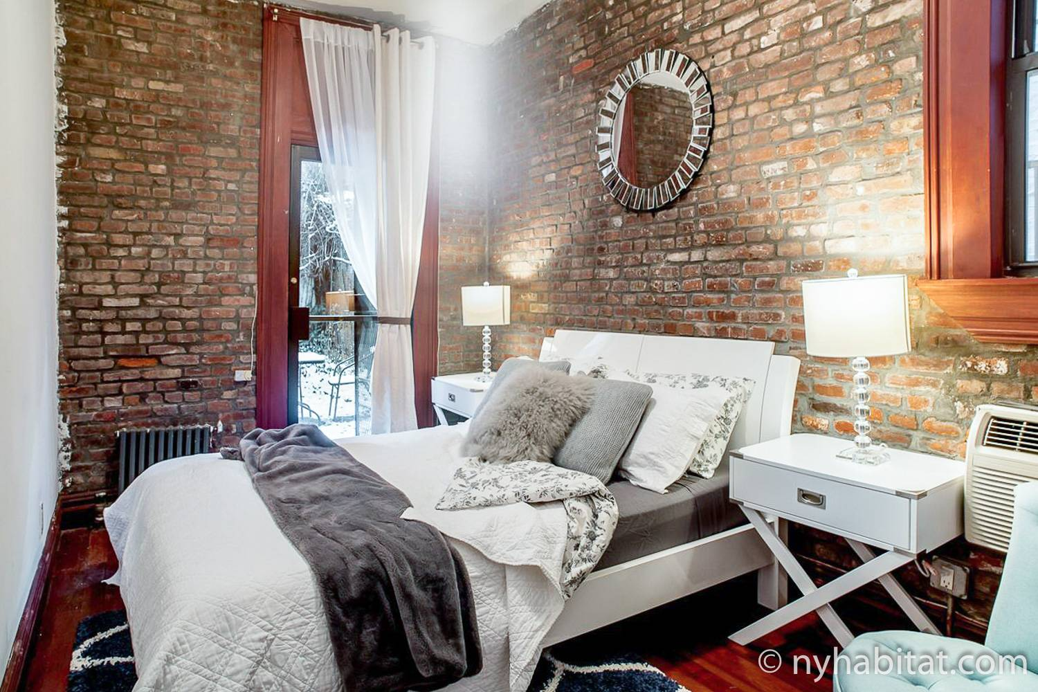 Image of bedroom in NY-16546 with queen-sized bed, mirror and back door