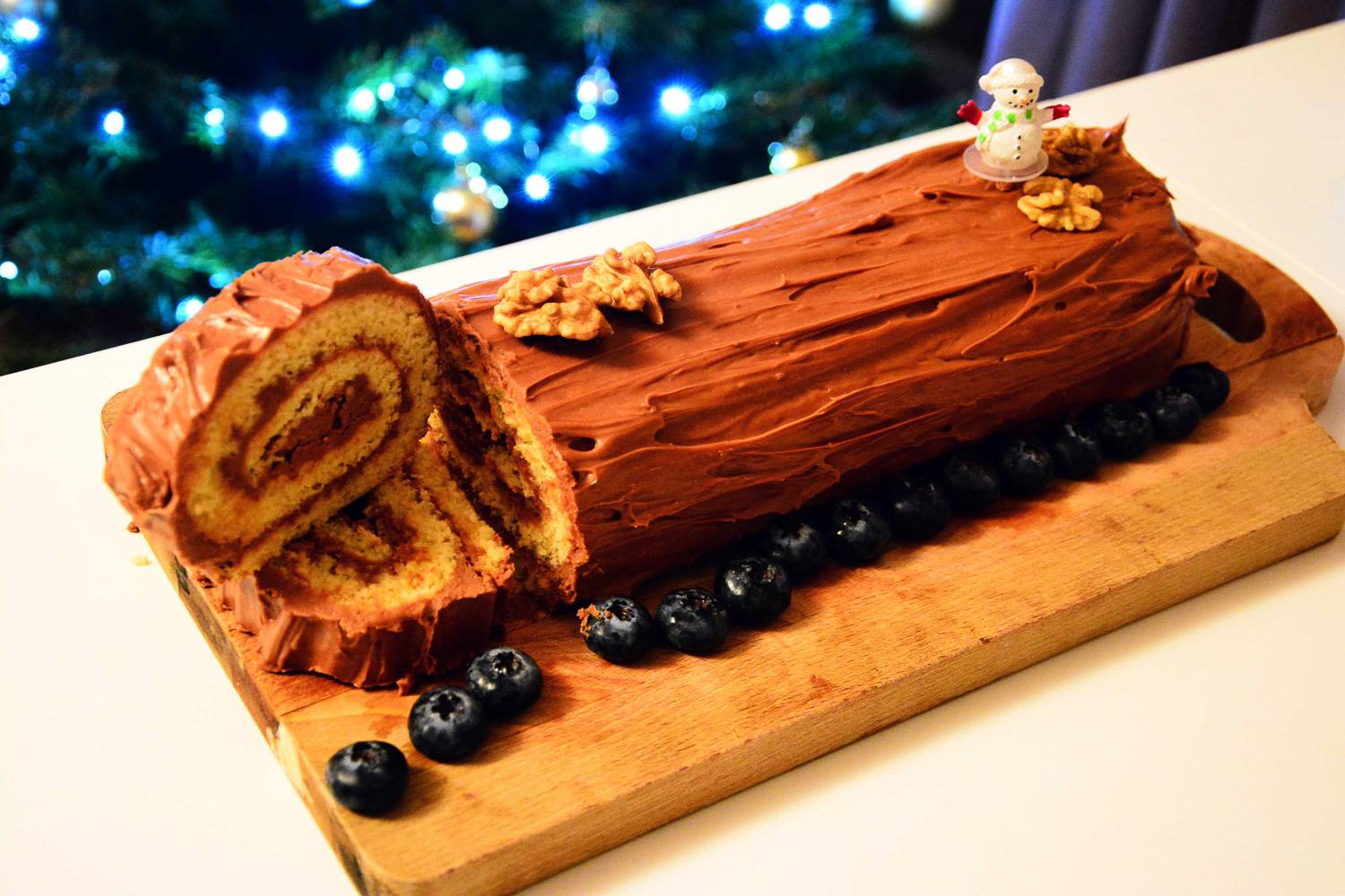 Image of a Yule log cake topped with a snowman figurine for the holidays.