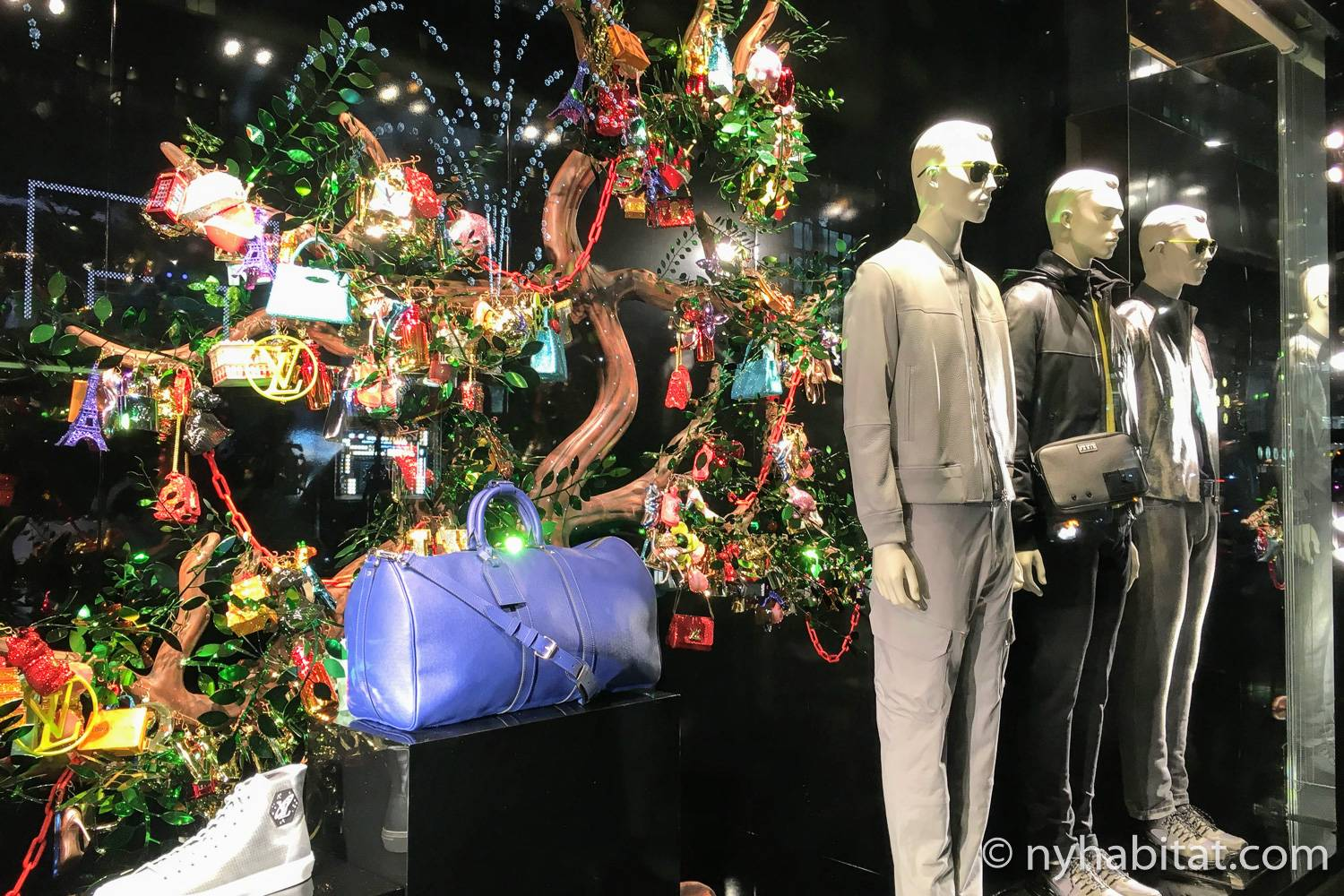 Image of Louis Vuitton's 2018 holiday window with decorated tree and mannequins.