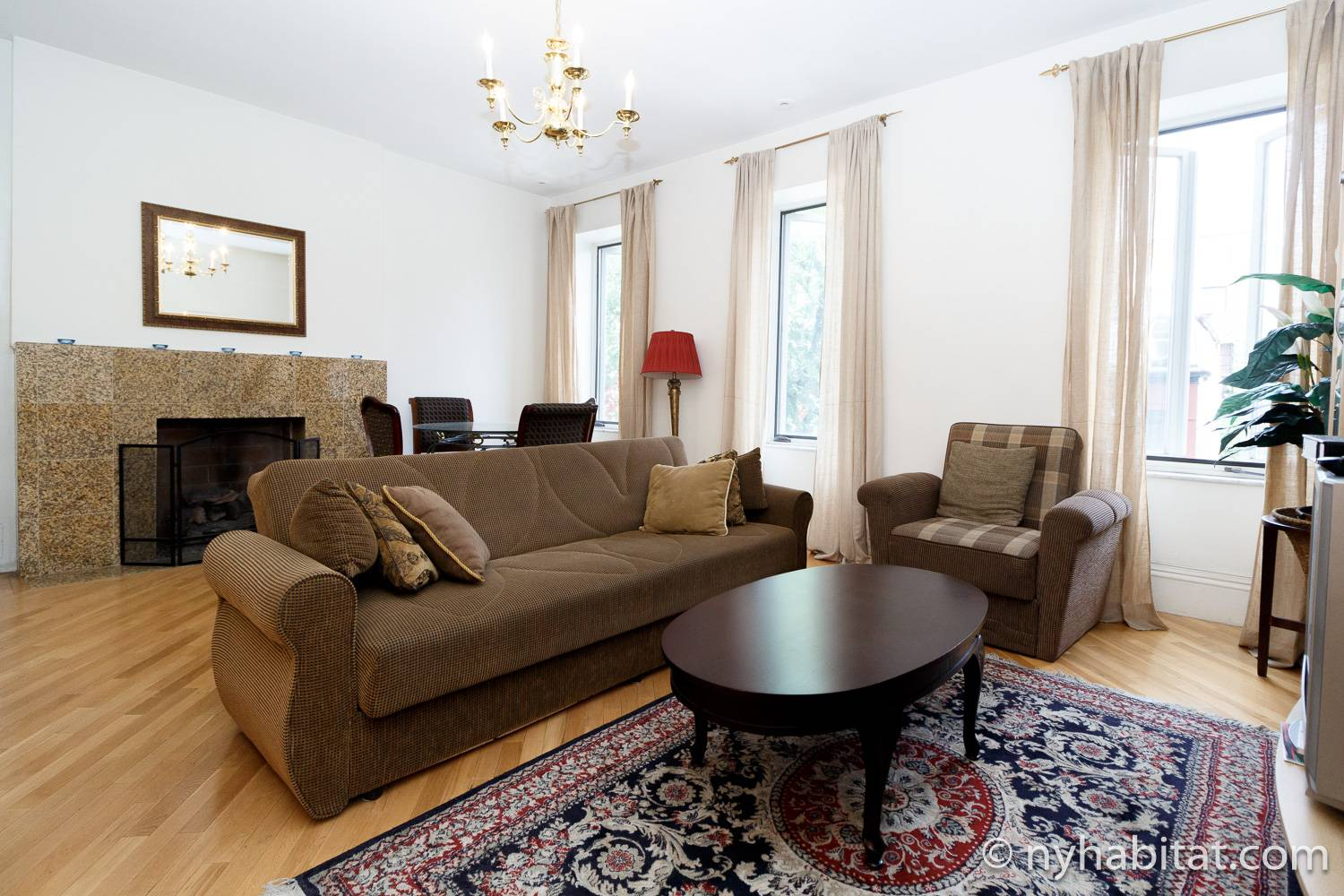 Image of living room in NY-12256 with sofa, coffee table, and working fireplace.