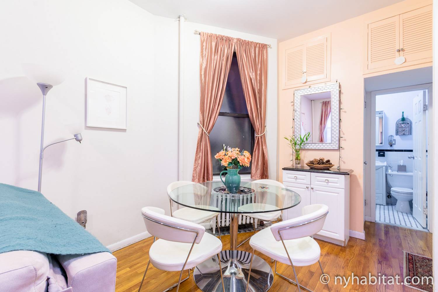 Image of living area in NY-15238 with table and chairs and flowers.