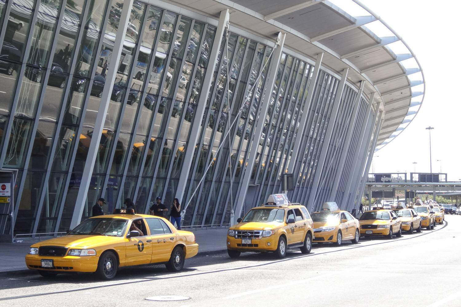 Image of NYC yellow taxis waiting to pick up riders at the curb of JFK airport.