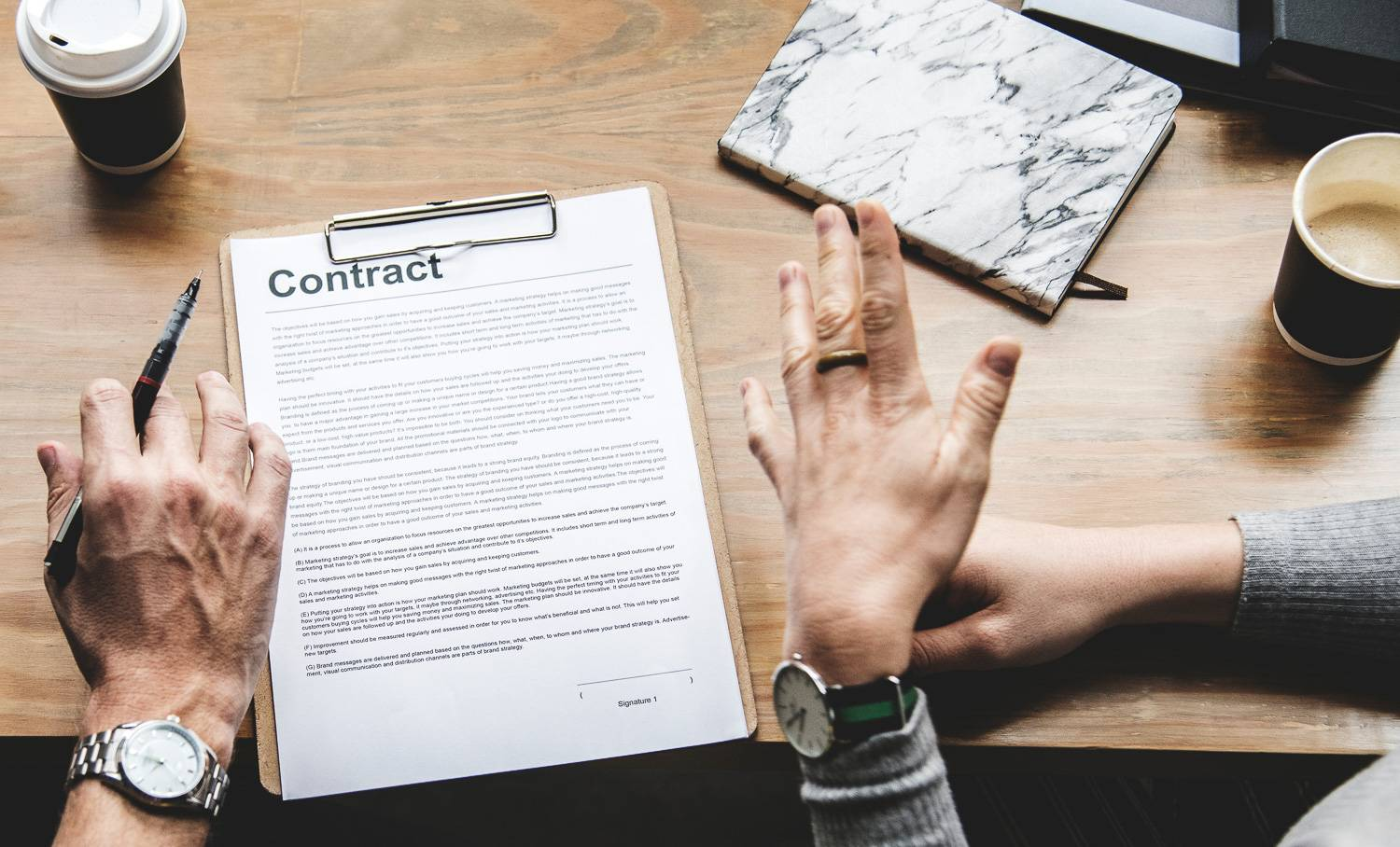 Image of two people's hands in the middle of a discussion over a rental contract.