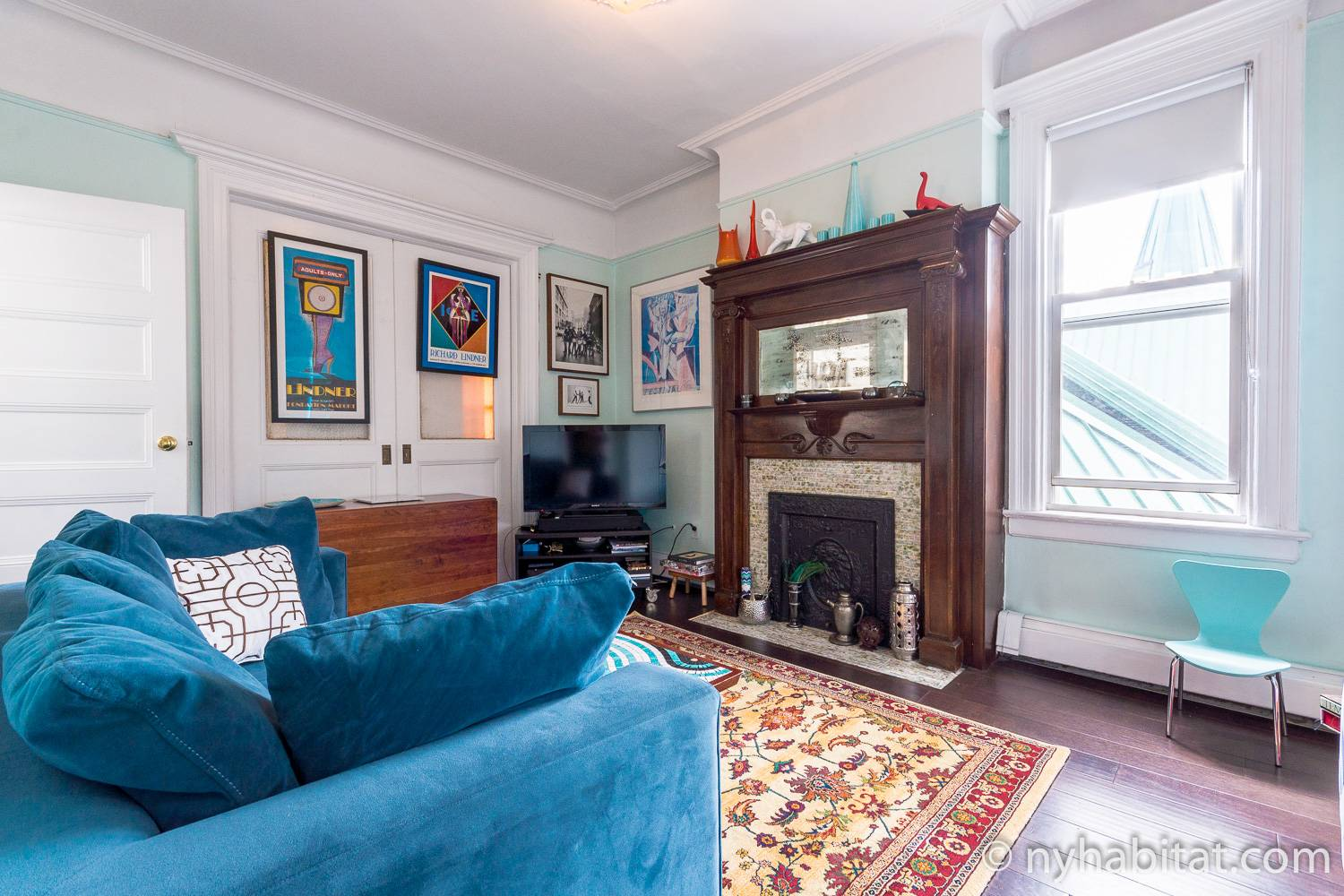 Image of living area of NY-17230 with sofa, decorative fireplace, television, area rug and artwork.