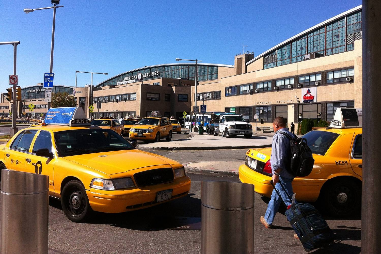 Image of yellow taxis waiting to pick up travelers at the curb of LaGuardia Airport and a traveler with a suitcase.