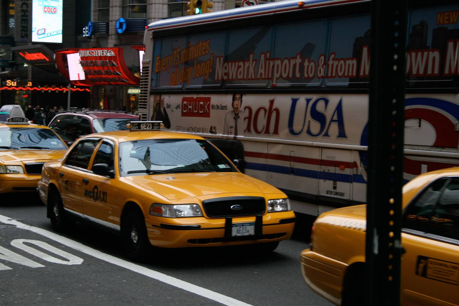 Image of yellow NYC taxi in front of Newark Airport Express Coach shuttle bus.