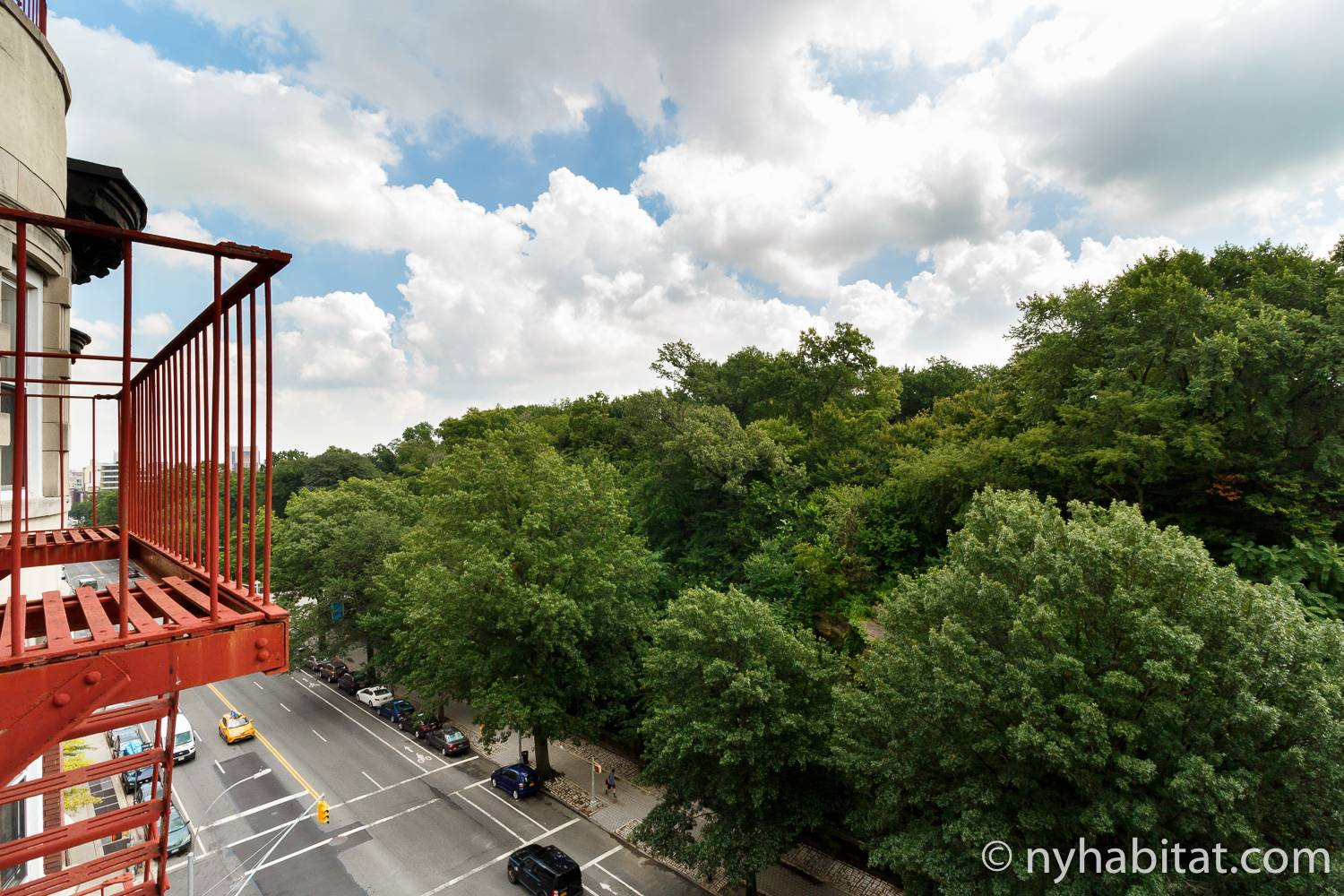 Image of a red painted fire escape outside apartment NY-14853 overlooking Central Park.