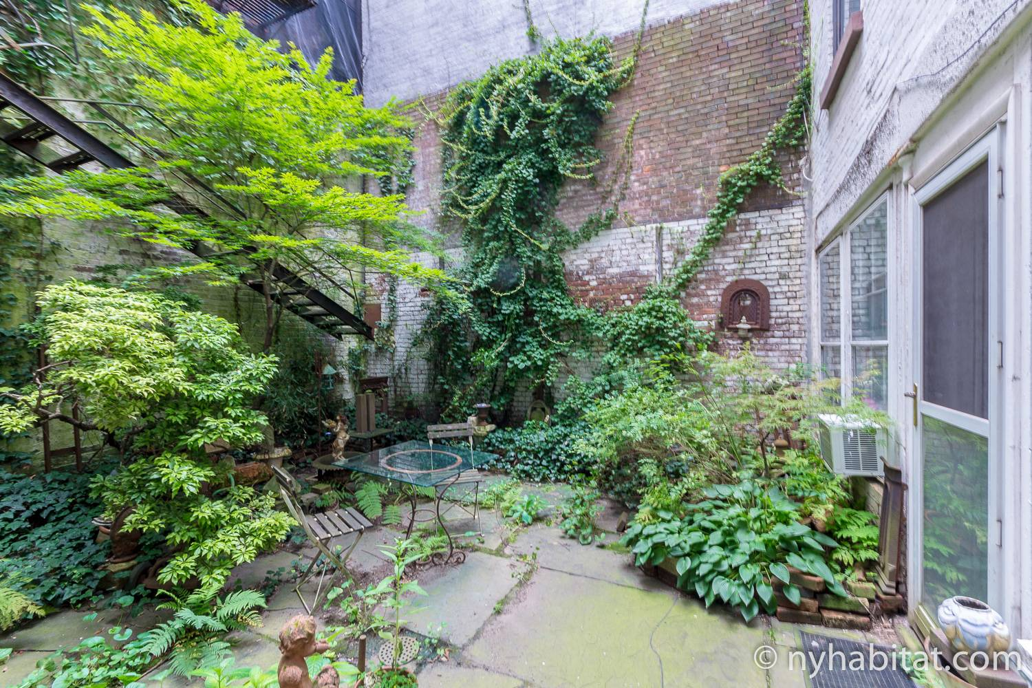 Image of garden area in NY-15343 with outdoor patio and table and chairs.