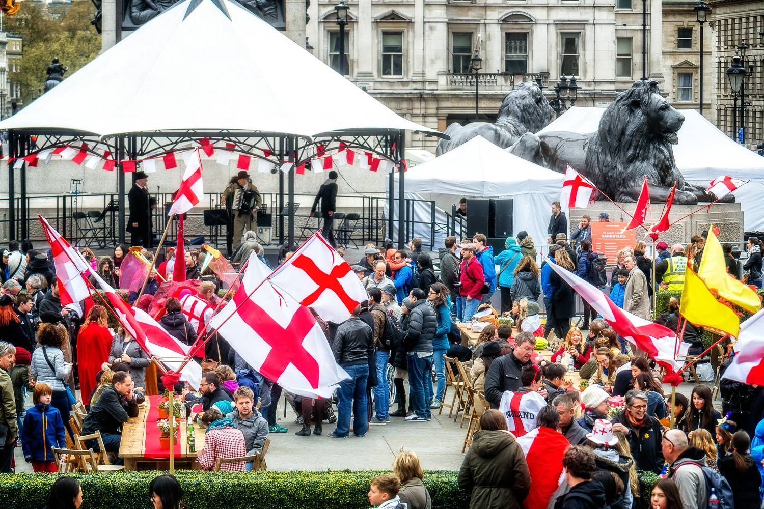 Image of people gathered for St. George's day in Trafalgar Square with tents and English flags.